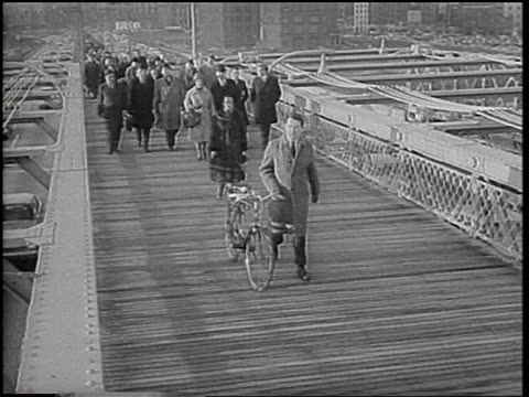 crowd of people walking across brooklyn bridge during transit strike / man pushes bicycle - brooklyn bridge stock videos & royalty-free footage