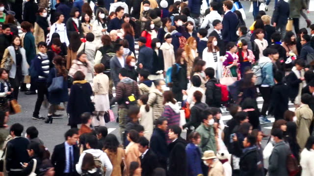 Crowd of people walking across the Shibuya crossing in Tokyo