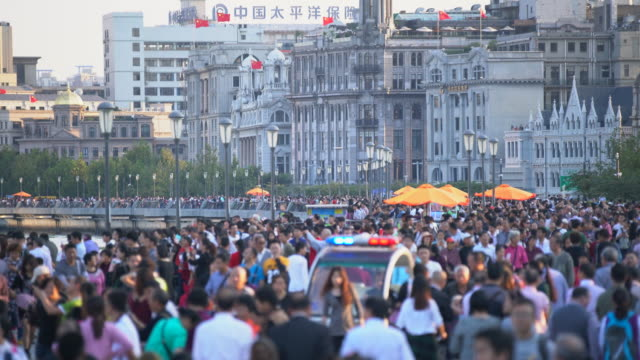 ws crowd of people walking along the bund in shanghai - chinese flag stock videos & royalty-free footage