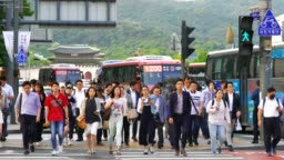 Crowd of people walking during the traffic light with Gwanghwamun Plaz in Seoul, South Korea