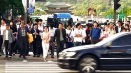 Crowd of people walking during the traffic light with Gwanghwamun Plaz in Seoul