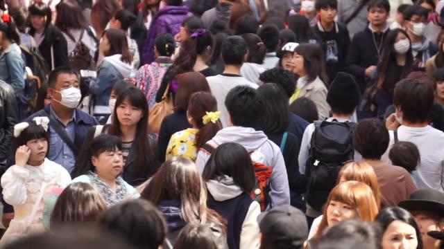 Crowd of people walking in a busy street in Tokyo
