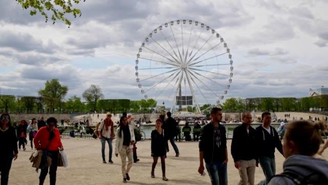 Crowd of people walking through the Tuileries Garden in Paris, France