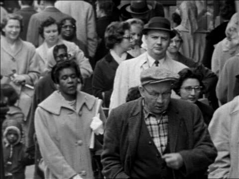 stockvideo's en b-roll-footage met b/w 1963 crowd of people walking toward camera on city sidewalk / documentary - 1963