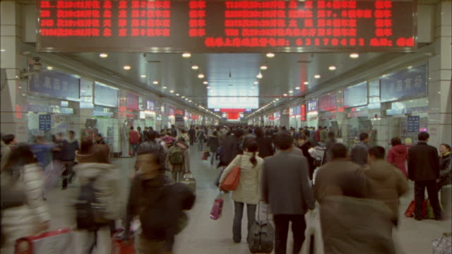 ms, t/l, crowd of people walking under shanghai railway station's information board, shanghai, china - railway station stock videos and b-roll footage
