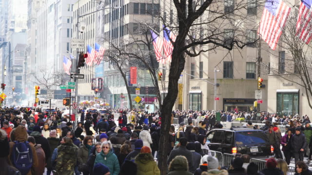 vídeos de stock, filmes e b-roll de a crowd of people walks down and crosses the fifth avenue around the saks fifth avenue, rockefeller center and saint patrick's cathedral in christmas holiday seasons at midtown manhattan new york ny usa on dec. 25 2018. - centro rockefeller