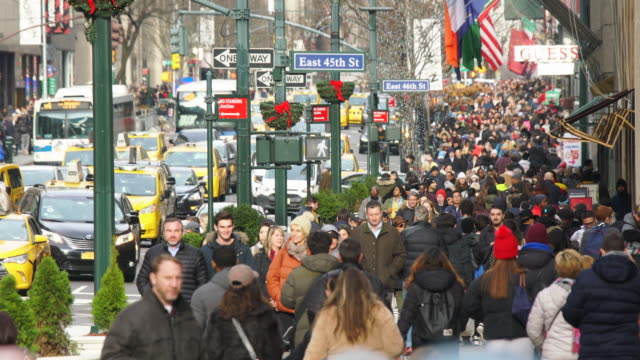 a crowd of people walks down the sidewalk and midtown manhattan heavy traffic goes through the fifth avenue during the winter holidays season at new york city ny usa on jan. 02 2020. - yellow taxi stock-videos und b-roll-filmmaterial