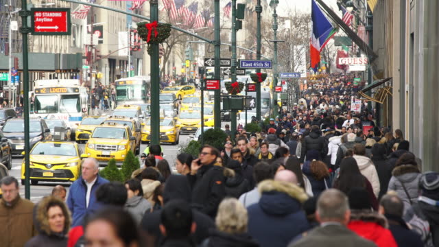 a crowd of people walks down the sidewalk and midtown manhattan heavy traffic goes through the fifth avenue during the winter holidays season at new york city ny usa on jan. 02 2020. - road junction stock videos & royalty-free footage