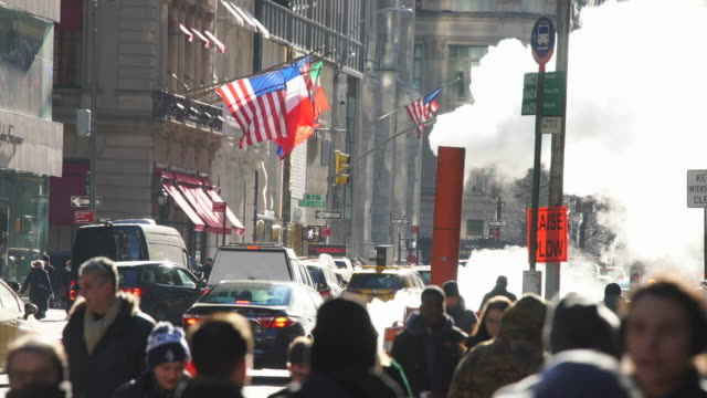 a crowd of people walks down the sidewalk and midtown manhattan traffic goes through the fifth avenue under the drifting steam among the buildings at new york city ny usa on jan. 09 2020. - yellow taxi stock videos & royalty-free footage