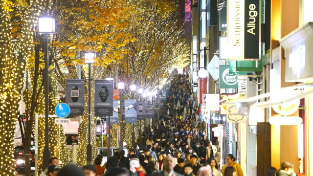 a crowd of people walks down the sidewalk beside the omotesando street among the illuminated rows of zelkova trees and many fashion boutiques for winter holydays season in the night at jingumae, shibuyatokyo japan on december 06 2017. - treelined stock videos & royalty-free footage