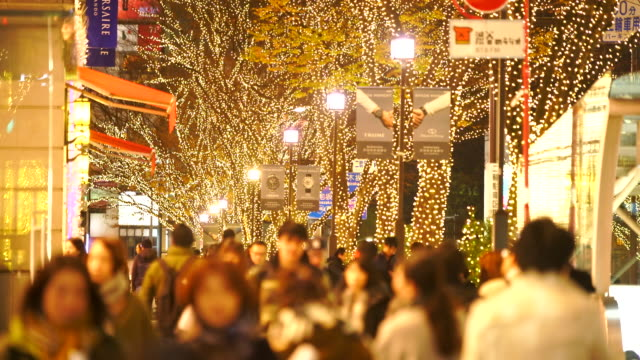 a crowd of people walks down the sidewalk beside the omotesando street station among the illuminated rows of zelkova trees and many fashion boutiques for winter holydays season in the night at kitaaoyama, minato tokyo japan on december 06 2017. - イルミネーション点の映像素材/bロール