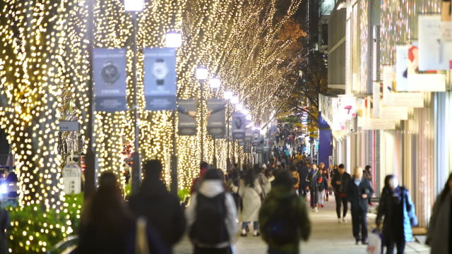 a crowd of people walks down the sidewalk beside the omotesando street among the illuminated rows of zelkova trees and many fashion boutiques for winter holydays season in the night at kitaaoyama, minato tokyo japan on december 06 2017. - avenue stock videos & royalty-free footage