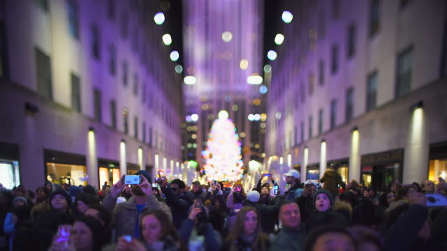 a crowd of people watches the saks fifth avenue christmas light show at midtown manhattan in the night at new york city ny usa on jan. 02 2020 - rockefeller center christmas tree stock videos & royalty-free footage