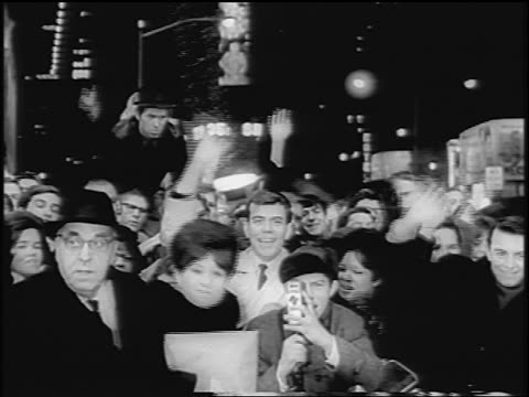 B/W 1967 crowd of people waving in Times Square at night / one man with film camera / NYC