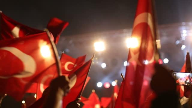 vidéos et rushes de foule de personnes agitant des drapeaux turcs dans la nuit au rassemblement politique / réunion - drapeau turc