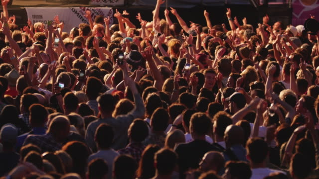 crowd of people with arms raised in air dancing cheering at music festival - arme hoch stock-videos und b-roll-filmmaterial