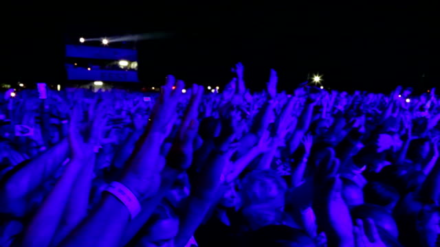 vídeos de stock e filmes b-roll de crowd of people with their hands up at a rock concert - evento de entretenimento