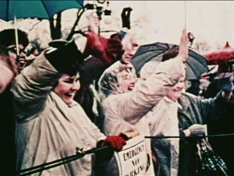 vídeos de stock, filmes e b-roll de 1962 crowd of people with umbrellas waving excitedly outdoors at parade for john glenn - 1962