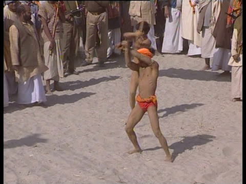 A crowd of pilgrims watch two dancers during Maha Kumbh Mela