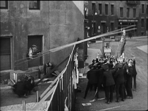 b/w 1922 crowd of policemen pushing down on end of ladder catapulting buster keaton into air - catapult stock videos & royalty-free footage