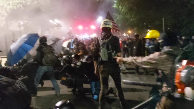 vídeos de stock e filmes b-roll de crowd of protesters gather around a newly-reinforced permitter fence outside the mark o. hatfield u.s. courthouse on july 22, 2020 in portland,... - portland oregon