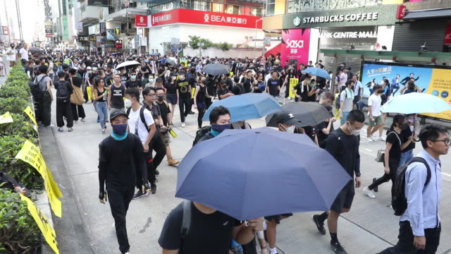 crowd of protestors marching along street of mong kok district hong kong china on monday aug 5 2019 - mong kok stock videos and b-roll footage