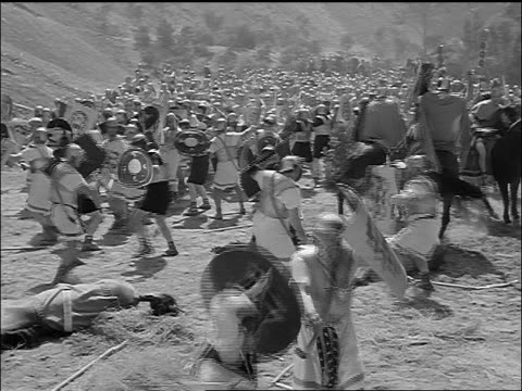 vídeos de stock, filmes e b-roll de b/w reenactment crowd of roman soldiers fight with swords / man on horse stabbed by spear / julius caesar (1953) - roman soldier