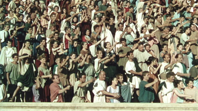 vídeos de stock, filmes e b-roll de crowd of romans raising arms + chanting + cheering in arena in ancient rome / quo vadis (1951) - roman soldier