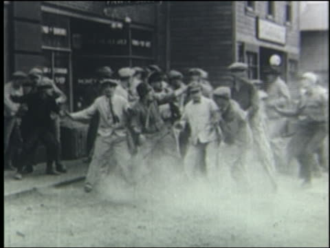 vídeos y material grabado en eventos de stock de b/w 1923 crowd of running men stops, turns + runs the other way on street - 1923