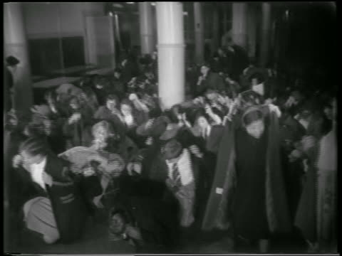 b/w 1951 crowd of schoolchildren crouch on floor cover themselves with jackets in defense drill - 1951年点の映像素材/bロール