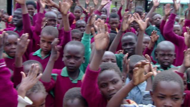 MS ZI PAN ZO Crowd of several Kenyan children performing song and  clapping / Kenya