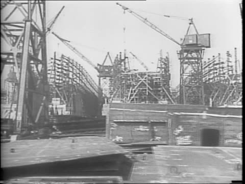 vidéos et rushes de crowd of shipyard workers arriving for work at the bethlehem fairchild shipyard / moving shot of the shipyard with partially constructed ships /... - 1942