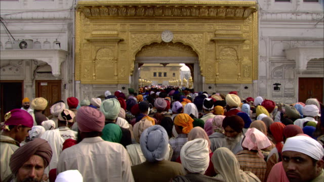 a crowd of sikhs enter the golden temple. - punjab region stock-videos und b-roll-filmmaterial