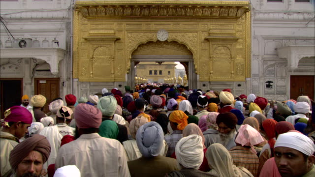 A crowd of Sikhs enter the Golden Temple.