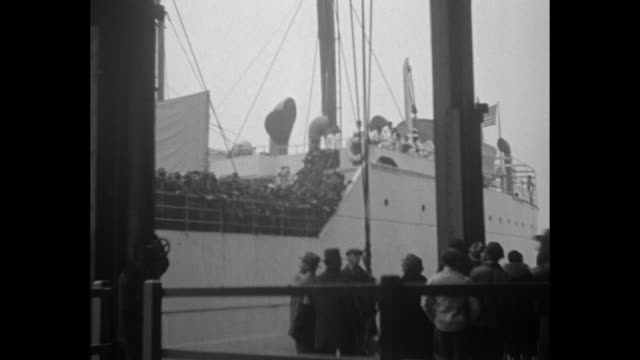 crowd of soldiers on deck of ship / two shots from pier of ship sailing with soldiers crowded on deck, people on pier in foreground / shot from on... - pier stock videos & royalty-free footage