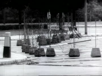 vidéos et rushes de crowd of soldiers standing in front of brandenburg gate / barbed wire attached to posts as the berlin wall is built / two men guiding large cement... - 1961