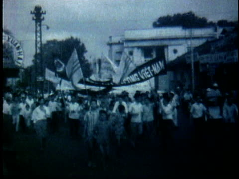 crowd of south vietnamese protesters carrying banners and marching down street during the early years of the vietnam war / south vietnam - vietnamkriget bildbanksvideor och videomaterial från bakom kulisserna