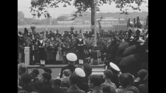 crowd of spectators on treelined street watch queenís mounted guard pass by sailors stand at attention / people in crowd wave as horsedrawn carriages... - coronation of queen elizabeth ii stock videos and b-roll footage