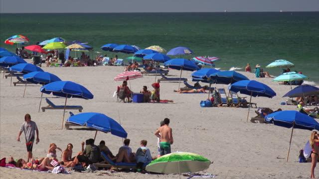crowd of sunbathers at south beach pavilion park in boca raton, florida - florida stati uniti video stock e b–roll