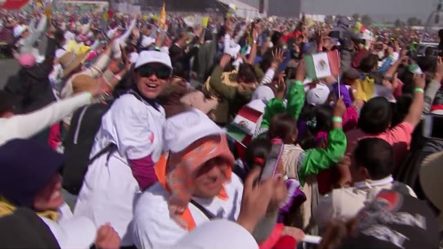 crowd of supporters stand behind barricade as pope francis passes through on his popemobile. they cheer and photograph him as the vehicle drives by... - ローマ法王専用車点の映像素材/bロール