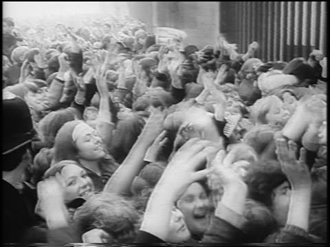 B/W 1965 crowd of teenagers waving at Beatles at gate of Buckingham Palace / London / newsreel