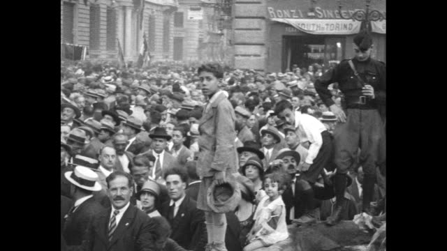 crowd of thousands of people, some waving handkerchiefs and men milling around on at street level / banners are carried through a large crowd / an... - benito mussolini stock videos & royalty-free footage