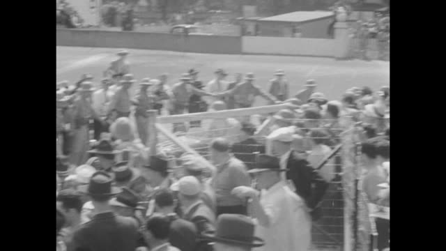 crowd of thousands seen behind a picket fence / vs cars driving on a track / vs car passes checkered flag is waved and it drives into the winners... - passing a note stock videos & royalty-free footage