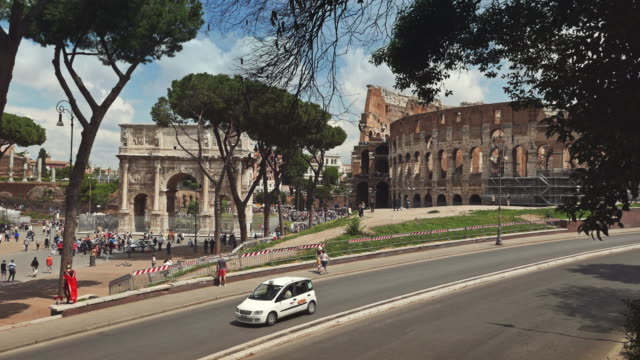 crowd of tourists by the coliseum of rome - arch of constantine stock videos and b-roll footage