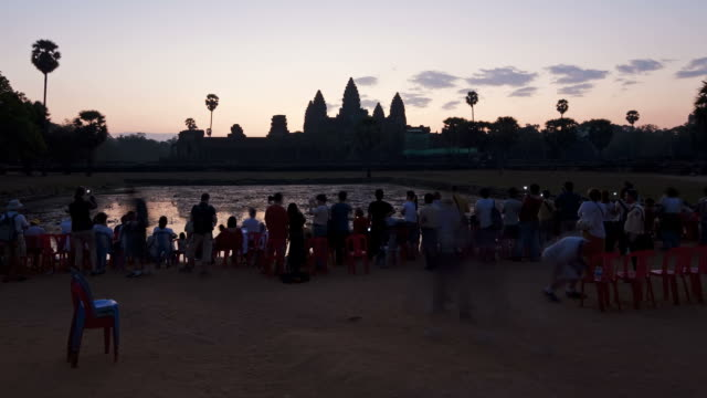 A crowd of tourists gather at the temples of Angkor Wat at golden hour.