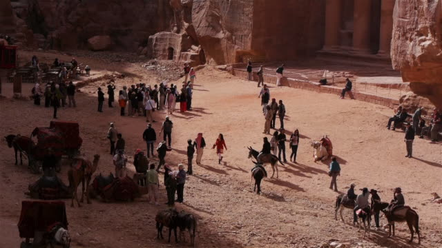 crowd of tourists in front of al-khazneh (the treasury) in petra, jordan. seen from above. - camel stock videos & royalty-free footage