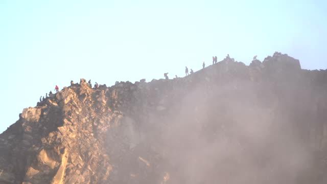 vídeos y material grabado en eventos de stock de multitud de viajeros es pequeño en un pico de la montaña sibayak bajo la niebla - acantilado