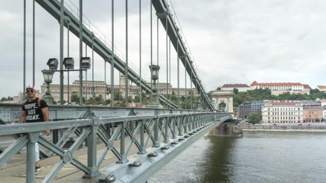 vidéos et rushes de tl: foule de voyageurs marchant sur le pont de la chaîne szechenyi à budapest, hongrie en week-end - pont à chaînes pont suspendu