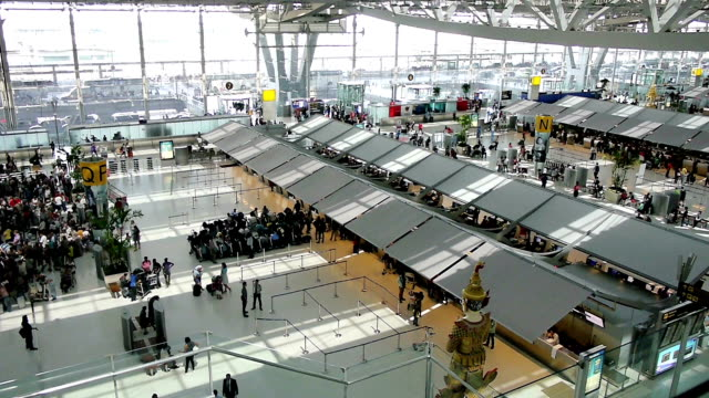 crowd of travelers at airport terminal check-in area - airline check in attendant stock videos & royalty-free footage