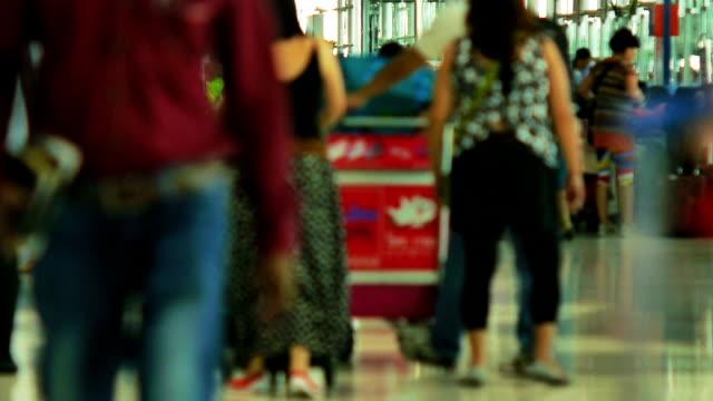 folla di viaggiatori all'aeroporto presso l'area check-in del terminal - addetto all'accettazione video stock e b–roll